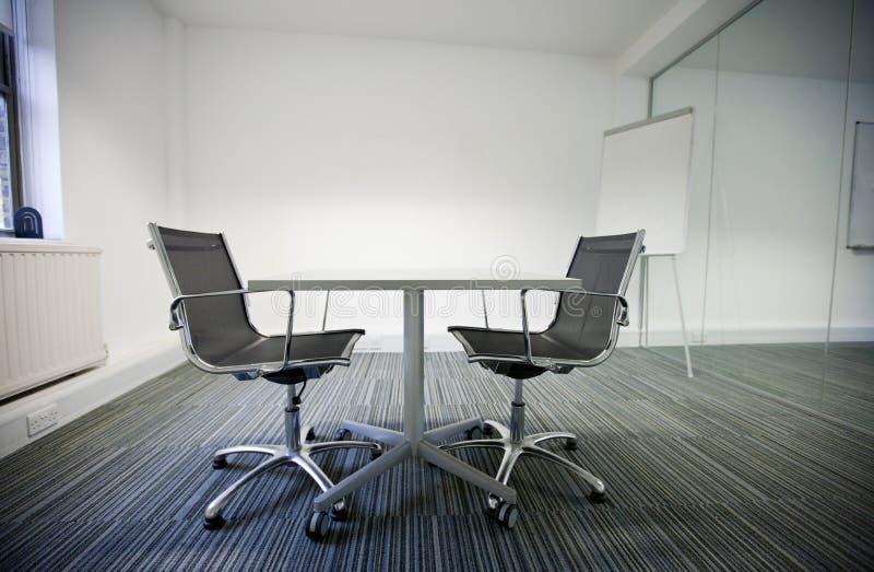 Vista lateral da tabela pequena e das duas cadeiras no escritório fotos de stock royalty free