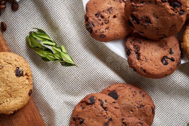 Vista lateral de cookies dos pedaços de chocolate em uma placa de madeira sobre o fundo rústico, foco seletivo imagem de stock