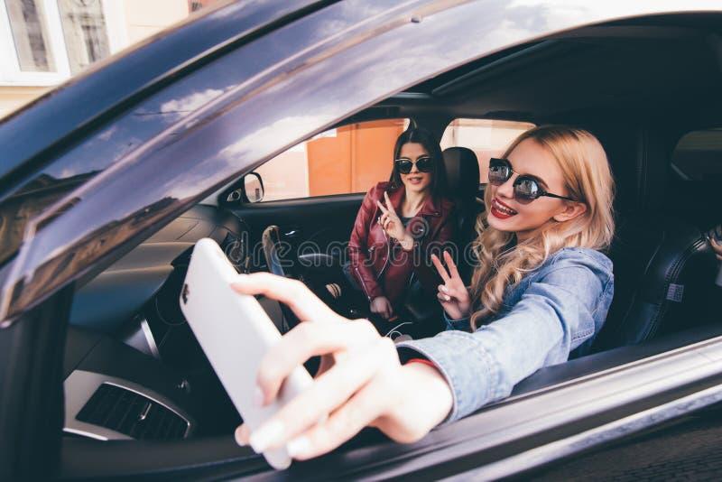 Vista lateral de cuatro mujeres alegres jovenes hermosas que hacen el selfie y que sonríen mientras que se sienta en coche junto imagen de archivo