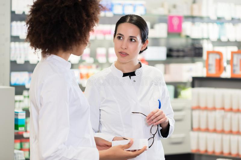 A vista lateral de dois dedicou os farmacêuticos que procuram o melhor medi imagens de stock