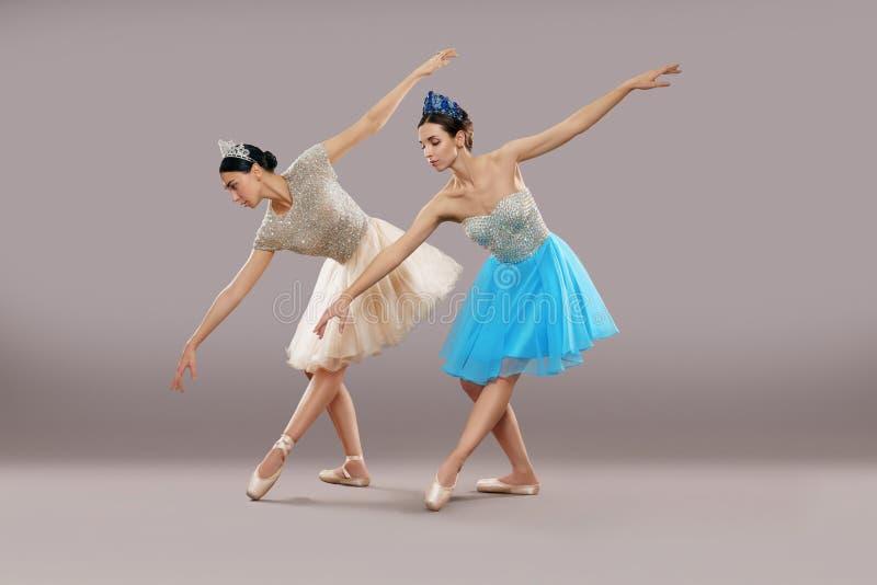 Vista lateral de dos bailarines que bailan y que doblan abajo en estudio imagenes de archivo