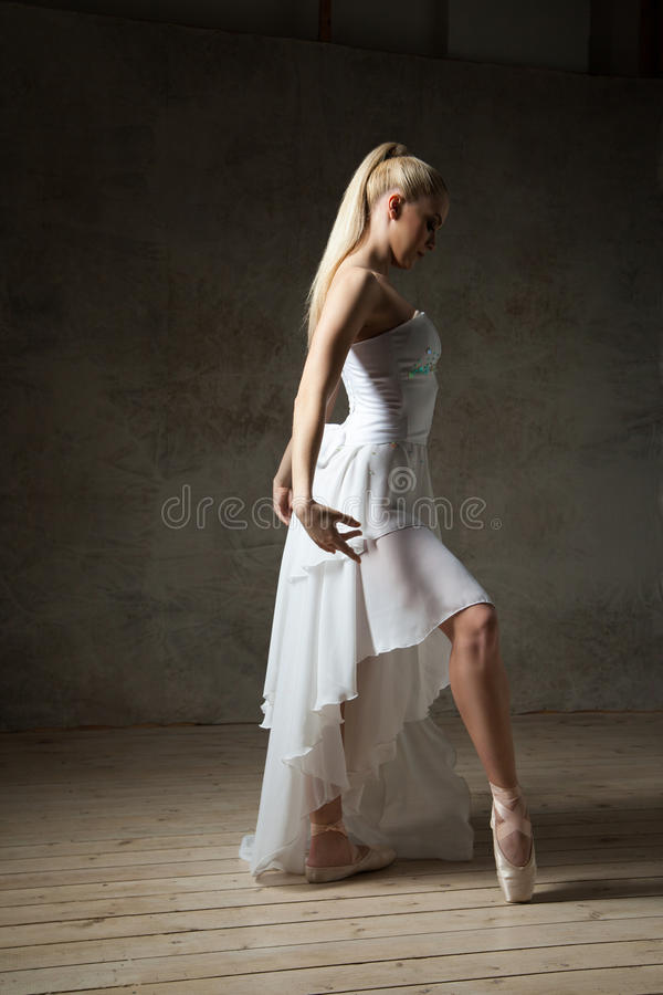 Vista lateral de la bailarina elegante que presenta en blanco en pointes foto de archivo
