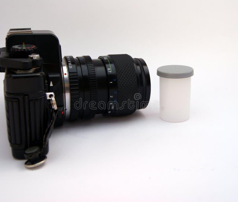 Vista lateral de la cámara y del carrete de película imagen de archivo