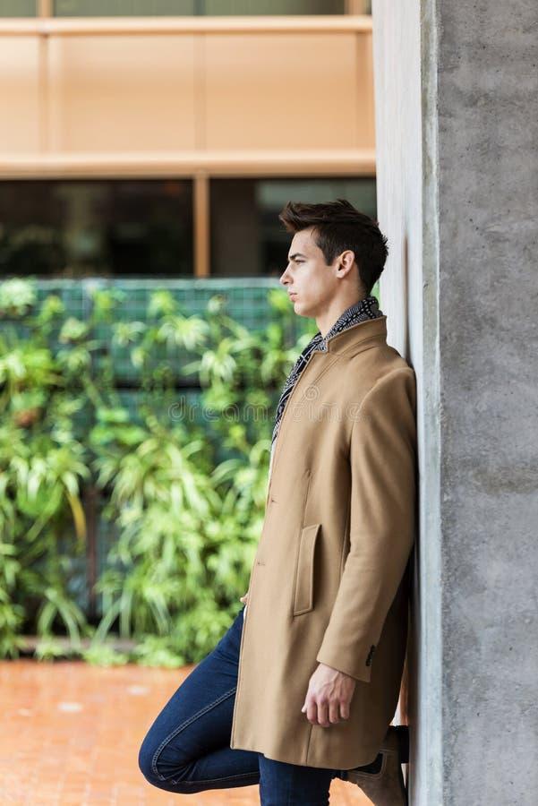 Vista lateral de la capa que lleva de moda y de la bufanda del hombre joven que se inclinan en una pared mientras que mira lejos imagen de archivo