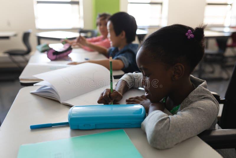 Vista lateral de la colegiala del negro de la neutralización que estudia y que se sienta en el escritorio en sala de clase fotografía de archivo