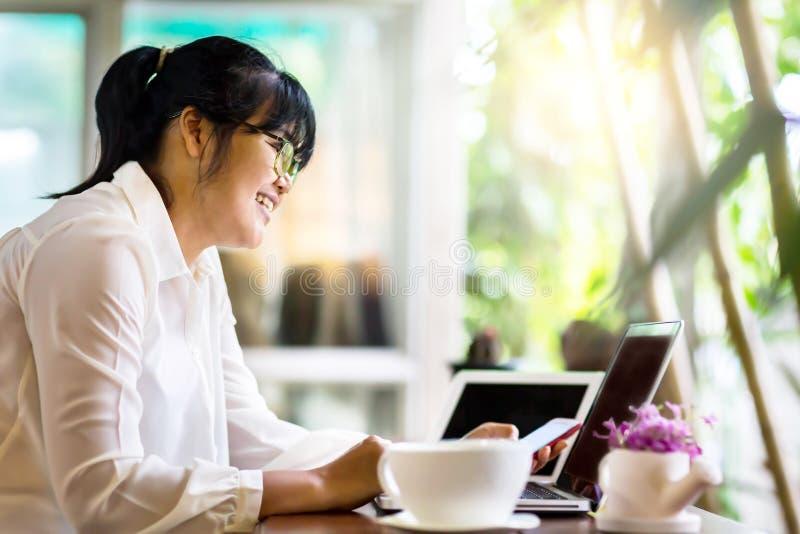 Vista lateral de la empresaria asiática que se sienta en la tabla larga en cafetería y que usa el ordenador portátil y que charla imagenes de archivo