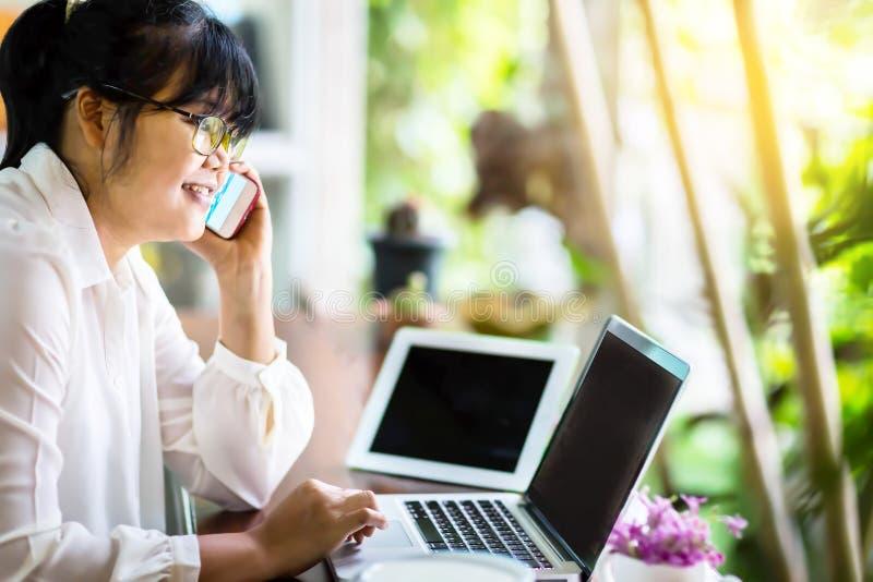 Vista lateral de la empresaria asiática que se sienta en la tabla larga en cafetería y que usa el ordenador portátil y que habla  imagen de archivo libre de regalías