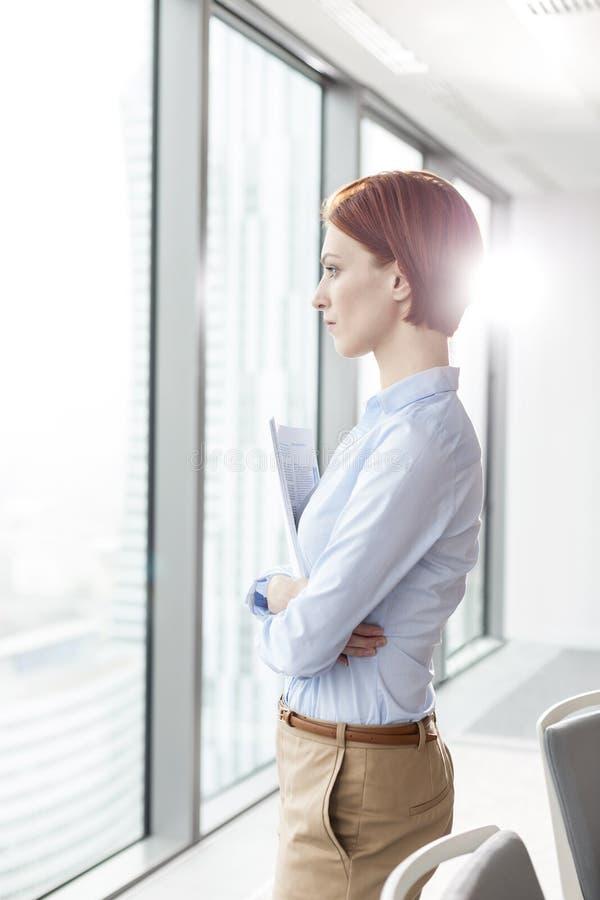 Vista lateral de la empresaria joven pensativa del pelirrojo que lleva a cabo documentos mientras que mira a través de ventana la fotografía de archivo libre de regalías