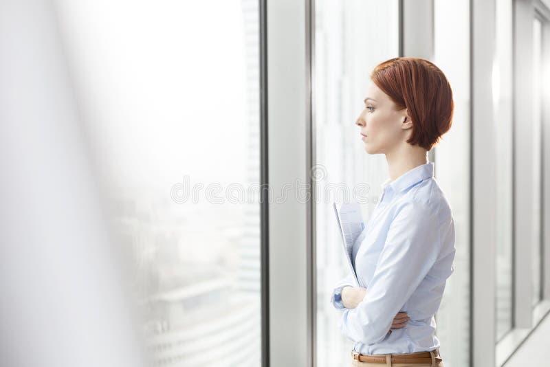 Vista lateral de la empresaria joven pensativa que lleva a cabo documentos mientras que mira a través de ventana la oficina foto de archivo