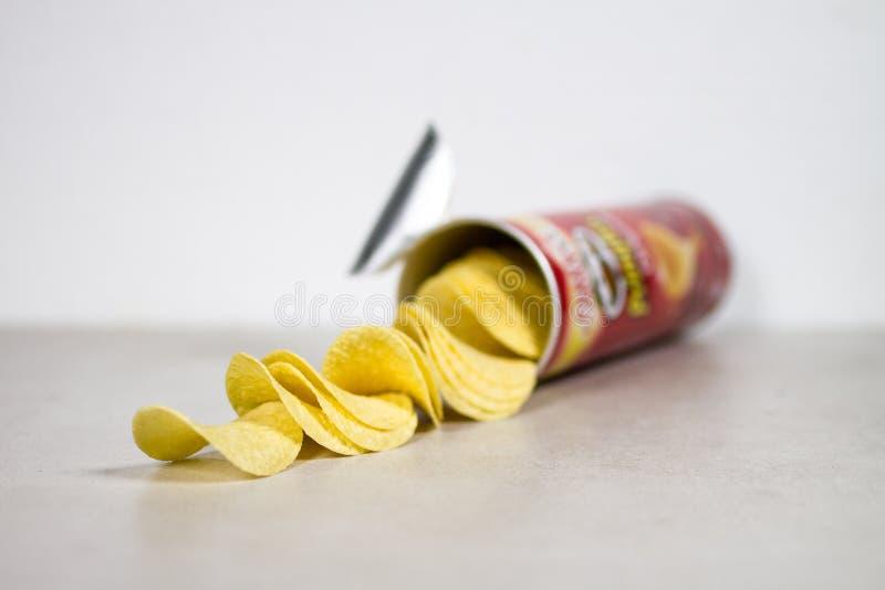 Vista lateral de la formación de la caja de Chips Coming Out Of The de la patata de Pringles sobre Gray Grey Whi fotos de archivo