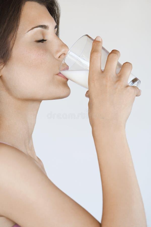 Vista lateral de la leche de consumo de la mujer foto de archivo libre de regalías