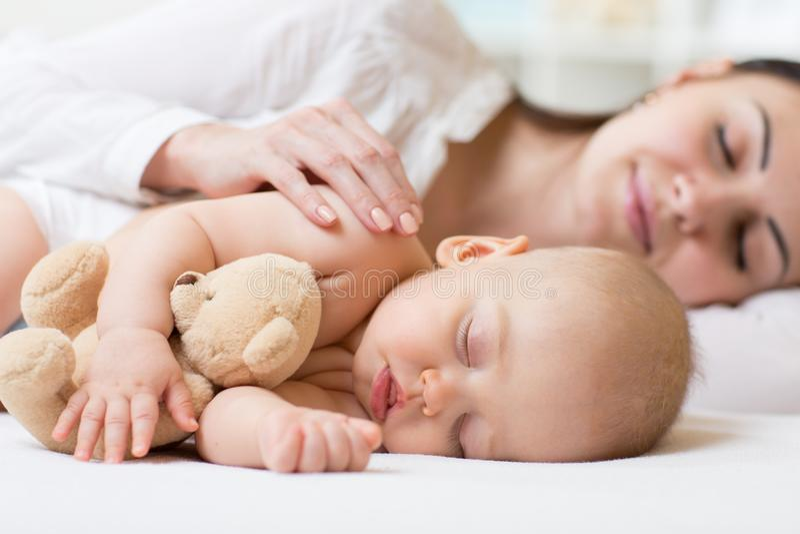 Vista lateral de la mamá joven hermosa y su del bebé lindo que duermen en cama en casa imagen de archivo libre de regalías
