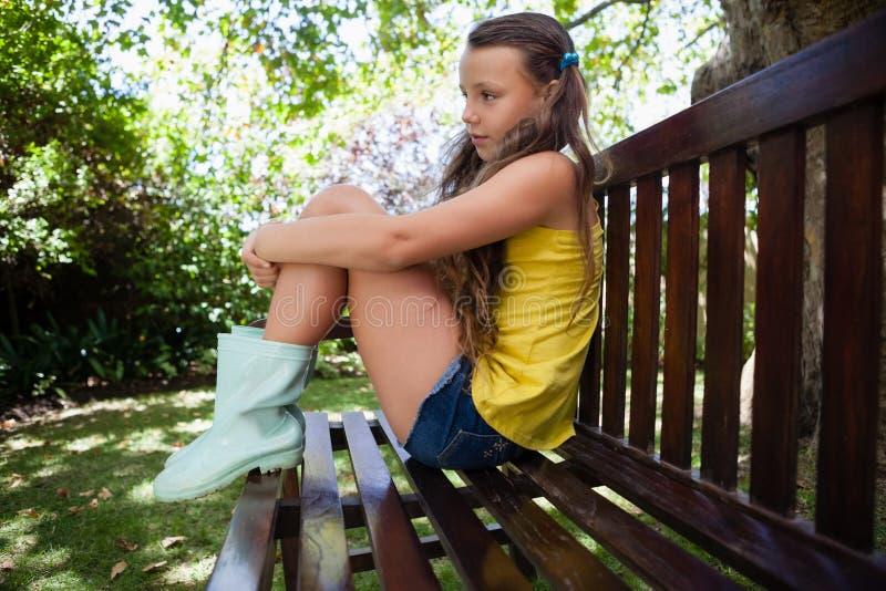 Vista lateral de la muchacha pensativa que se sienta en banco de madera fotos de archivo