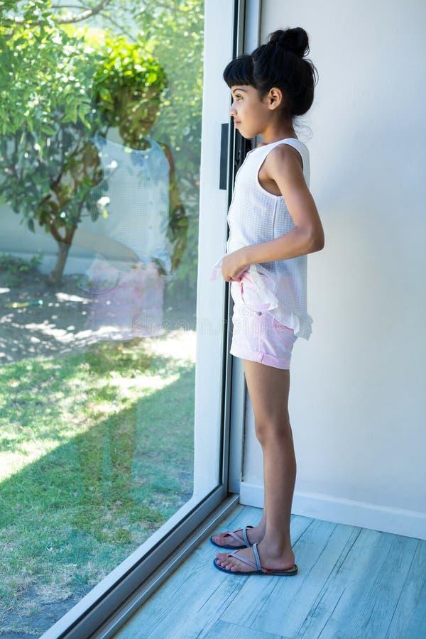 Vista lateral de la muchacha que mira a través de ventana fotos de archivo libres de regalías