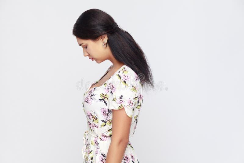 Vista lateral de la mujer adulta joven triste, castigada solamente en la pared gris fotografía de archivo libre de regalías