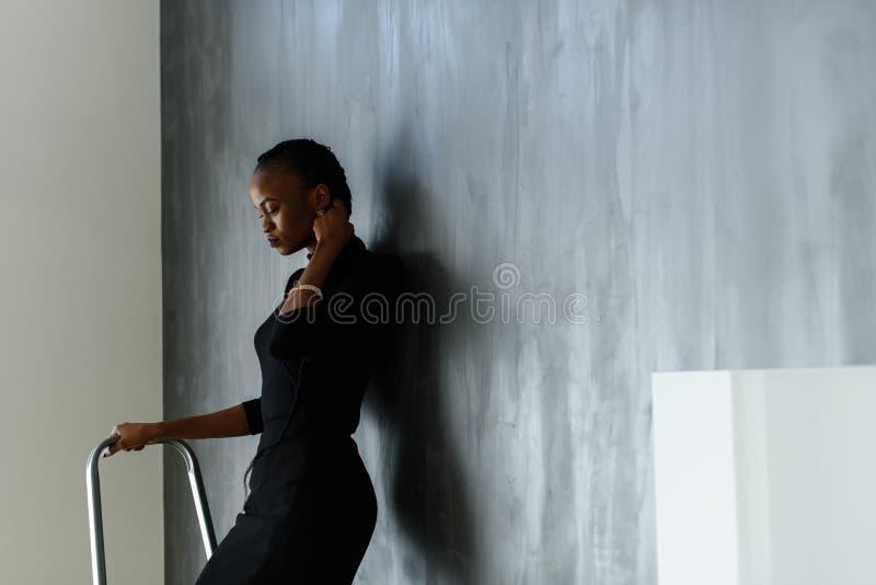 Vista lateral de la mujer americana bastante africana o negra que toca su trenza gruesa en fondo oscuro del estudio imagenes de archivo