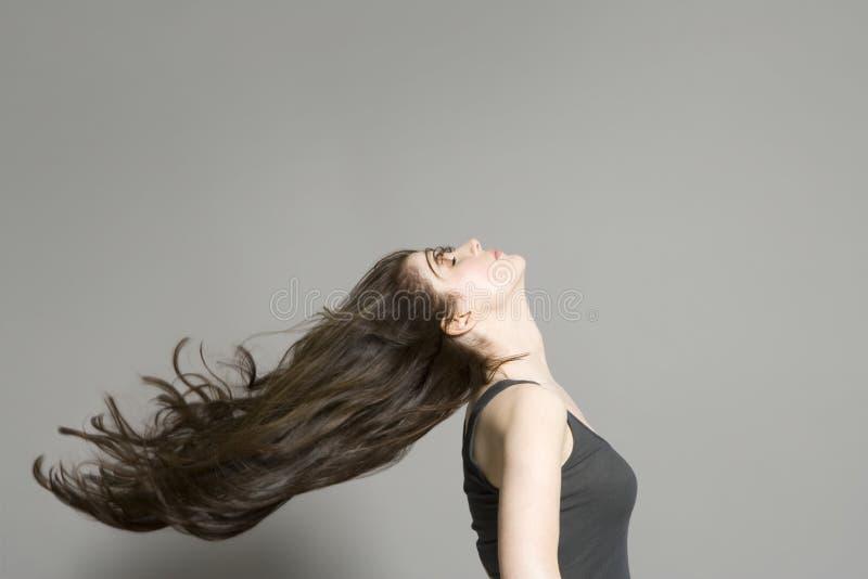 Vista lateral de la mujer con el pelo largo que sopla en viento imagen de archivo libre de regalías