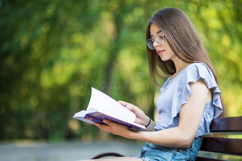Vista lateral de la mujer contenta en las lentes que se sientan en banco y el libro de lectura en parque fotos de archivo libres de regalías