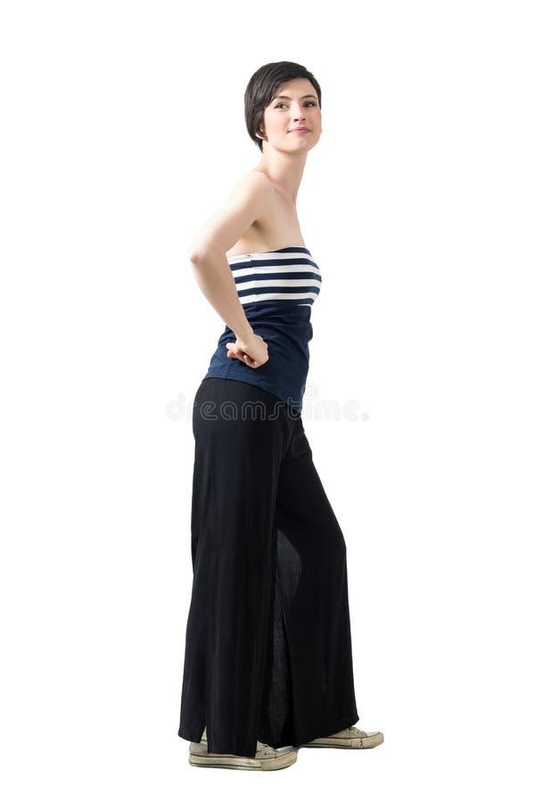 Vista lateral de la mujer de moda en los pantalones de la ancho-pierna y el top del apagado--hombro que presentan en la cámara fotos de archivo libres de regalías