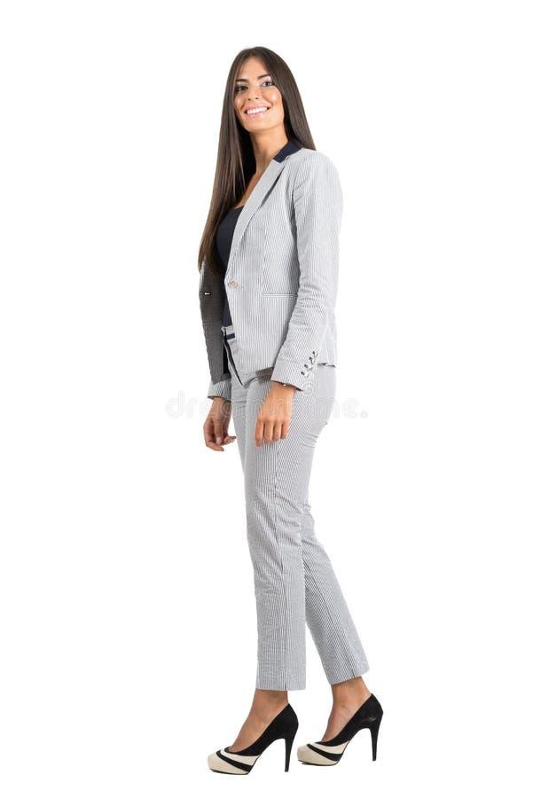 Vista lateral de la mujer de negocios joven sonriente que camina mirando la cámara imágenes de archivo libres de regalías