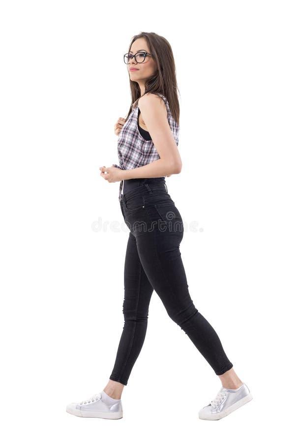 Vista lateral de la mujer elegante joven satisfecha confiada que camina y que mira para arriba a continuación fotos de archivo
