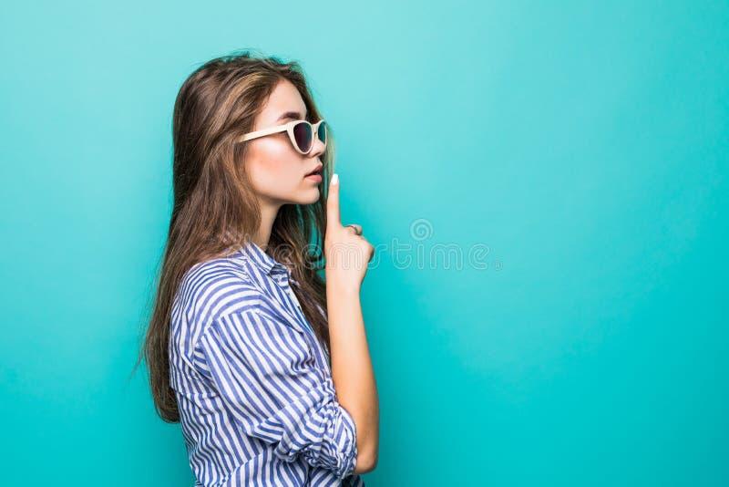 Vista lateral de la mujer en la camisa y las gafas de sol que muestran gesto del silencio sobre fondo azul fotos de archivo libres de regalías