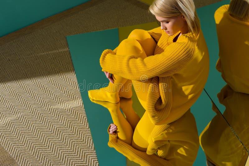 vista lateral de la mujer en suéter amarillo y las medias que se sientan en el espejo con la reflexión imagen de archivo