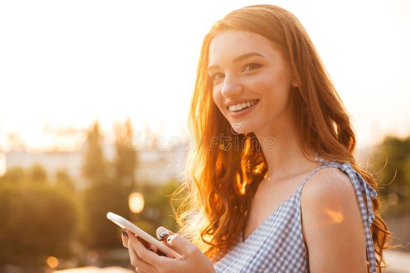 Vista lateral de la mujer feliz del jengibre de la belleza en vestido fotografía de archivo