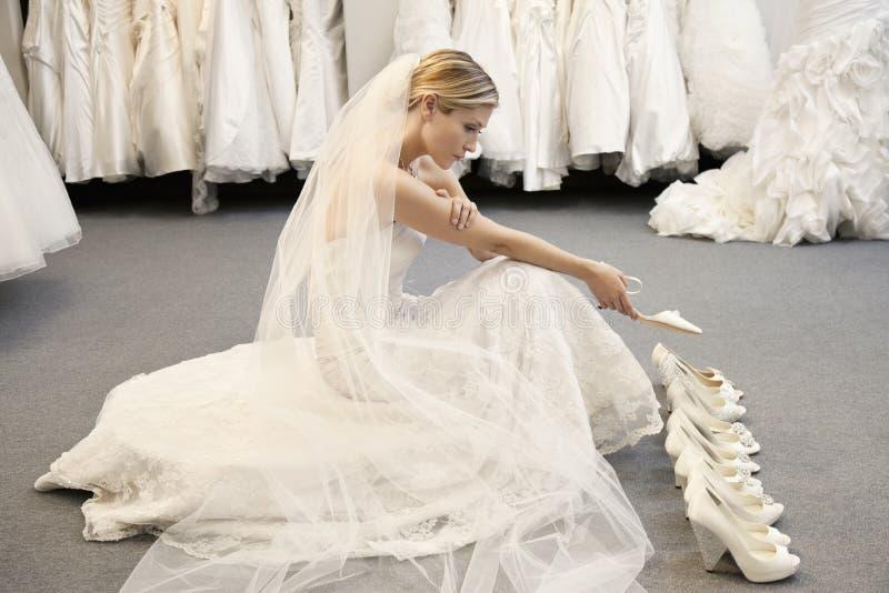 Vista lateral de la mujer joven en el vestido de boda confundido mientras que selecciona calzado fotografía de archivo