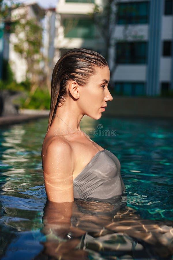 vista lateral de la mujer joven mojada atractiva foto de archivo