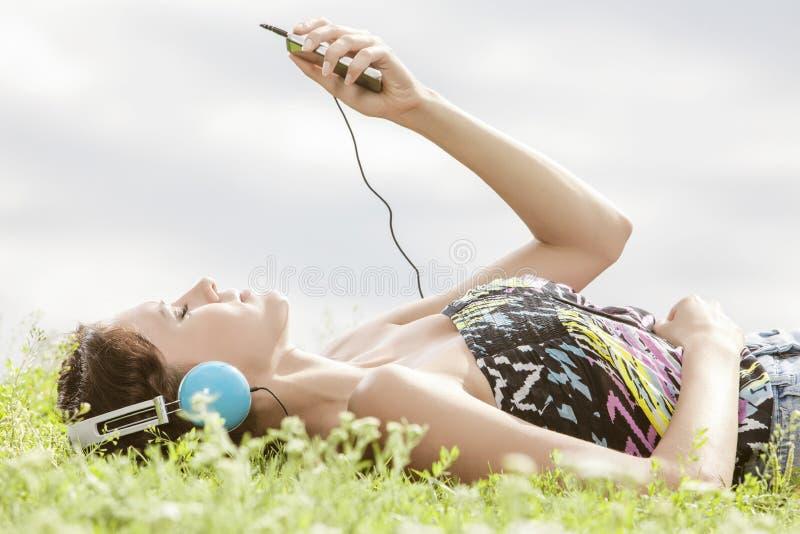 Vista lateral de la mujer joven que escucha la música con reproductor Mp3 mientras que miente en hierba contra el cielo fotografía de archivo