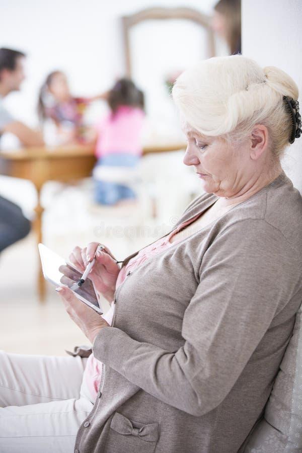 Vista lateral de la mujer mayor que usa la tableta digital en casa imagen de archivo