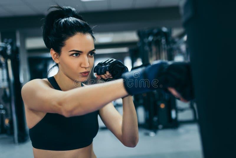 Vista lateral de la mujer morena atractiva fuerte que perfora un bolso con los guantes kickboxing en el entrenamiento del gimnasi foto de archivo libre de regalías