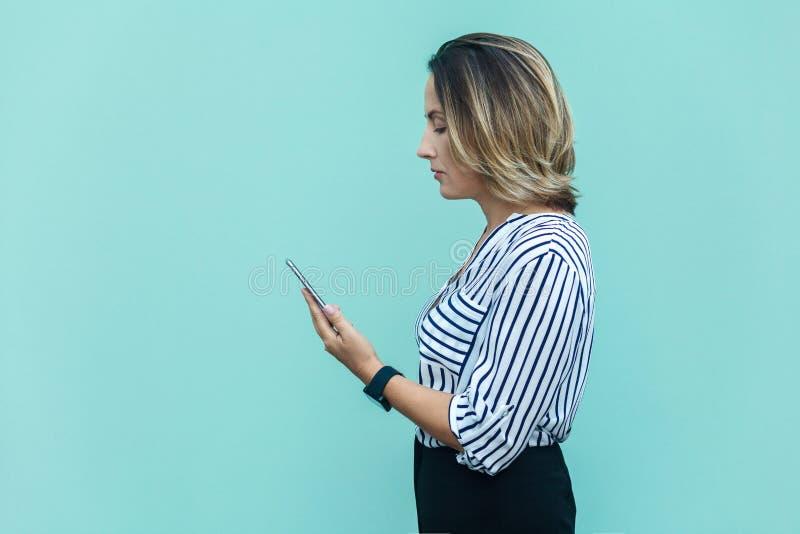 Vista lateral de la mujer de negocios infeliz, castigada solamente en la pared azul foto de archivo