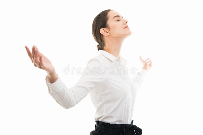 Vista lateral de la mujer de negocios joven que se coloca con los brazos abiertos imagen de archivo libre de regalías