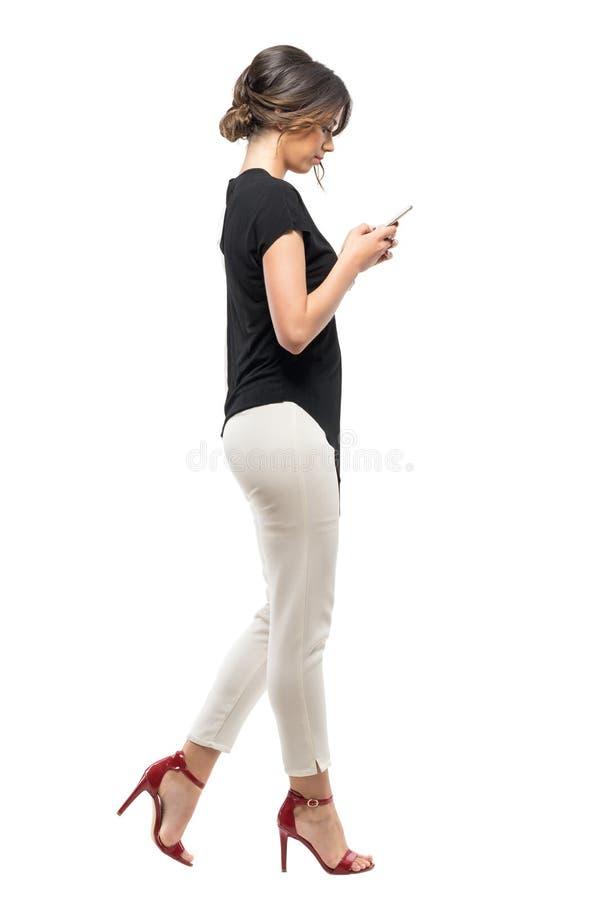 Vista lateral de la mujer de negocios ocupada en traje formal que camina y que mecanografía en el teléfono móvil foto de archivo