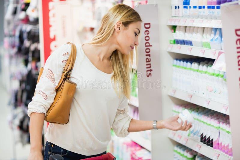 Vista lateral de la mujer que elige el desodorante foto de archivo libre de regalías