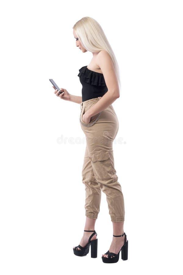 Vista lateral de la mujer rubia atractiva que usa el mensaje elegante de la lectura del teléfono foto de archivo libre de regalías