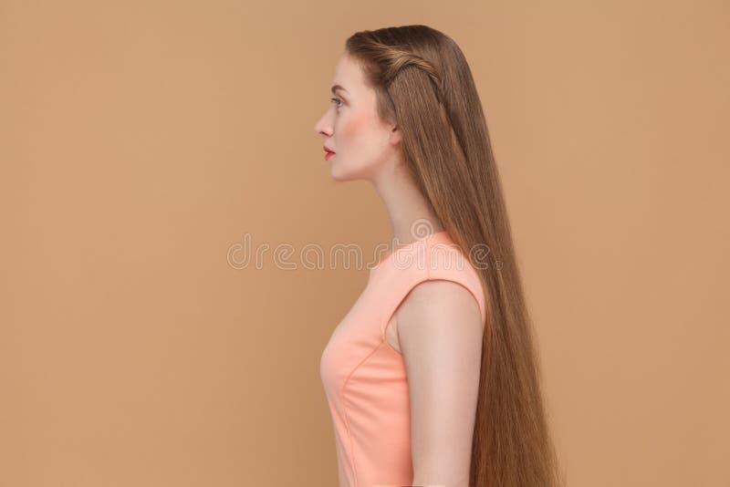 Vista lateral de la mujer seria hermosa con el pelo marrón largo fotos de archivo libres de regalías