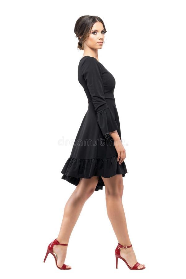 Vista lateral de la mujer sofisticada en vestido negro que camina y que mira la cámara imágenes de archivo libres de regalías