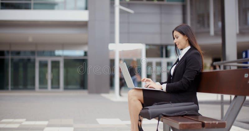 Vista lateral de la mujer solamente con el ordenador portátil en banco imágenes de archivo libres de regalías