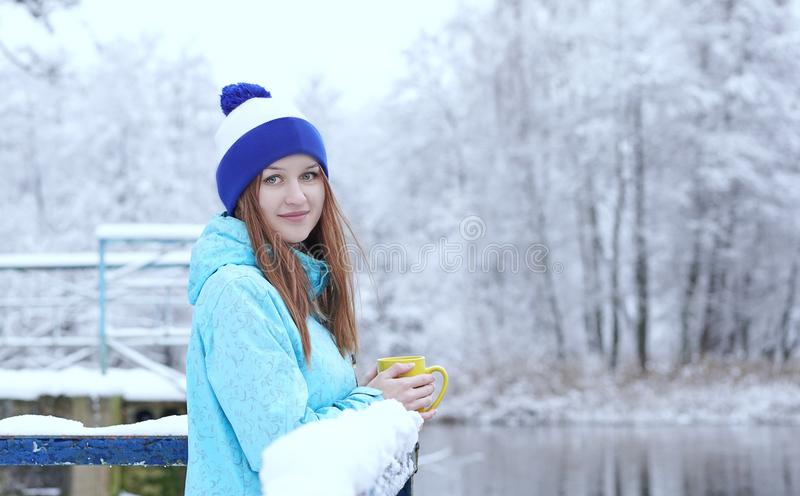 Vista lateral de la mujer sonriente joven con una taza de té o de café caliente en orilla del agua nevosa del invierno imagen de archivo libre de regalías