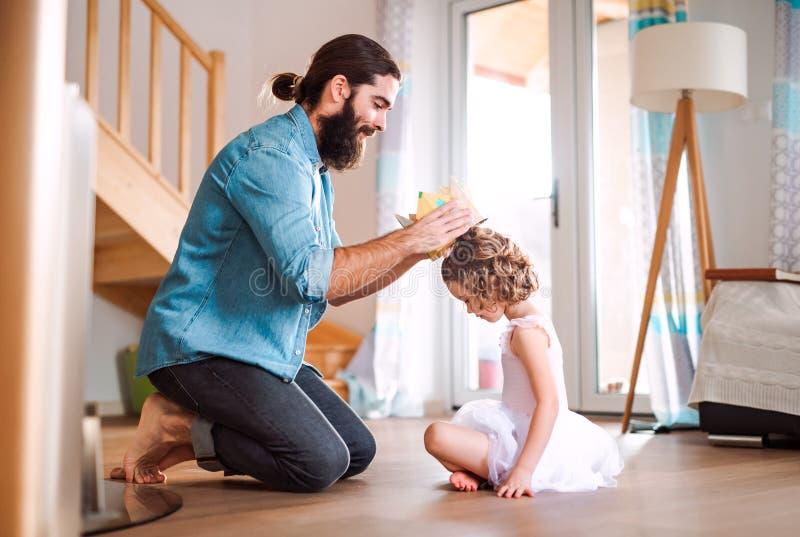 Vista lateral de la peque?a muchacha con una corona de la princesa y un padre joven en casa, jugando imagenes de archivo