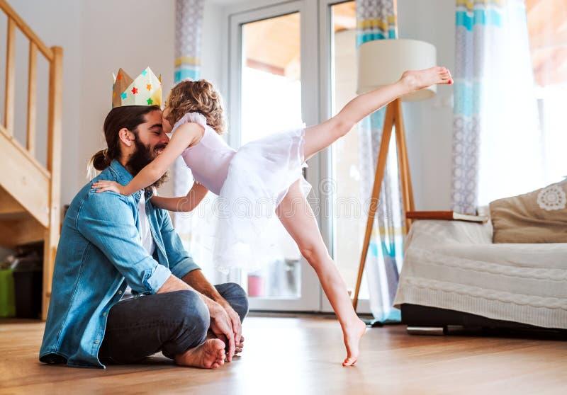 Vista lateral de la peque?a muchacha con una corona de la princesa y un padre joven en casa, jugando imagen de archivo