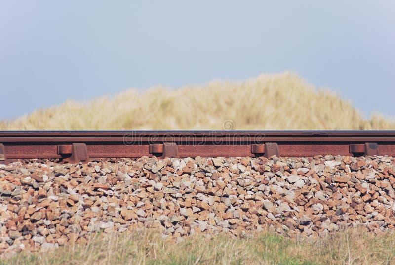 Vista lateral de la pista ferroviaria entre las hierbas de la duna de arena imagen de archivo libre de regalías