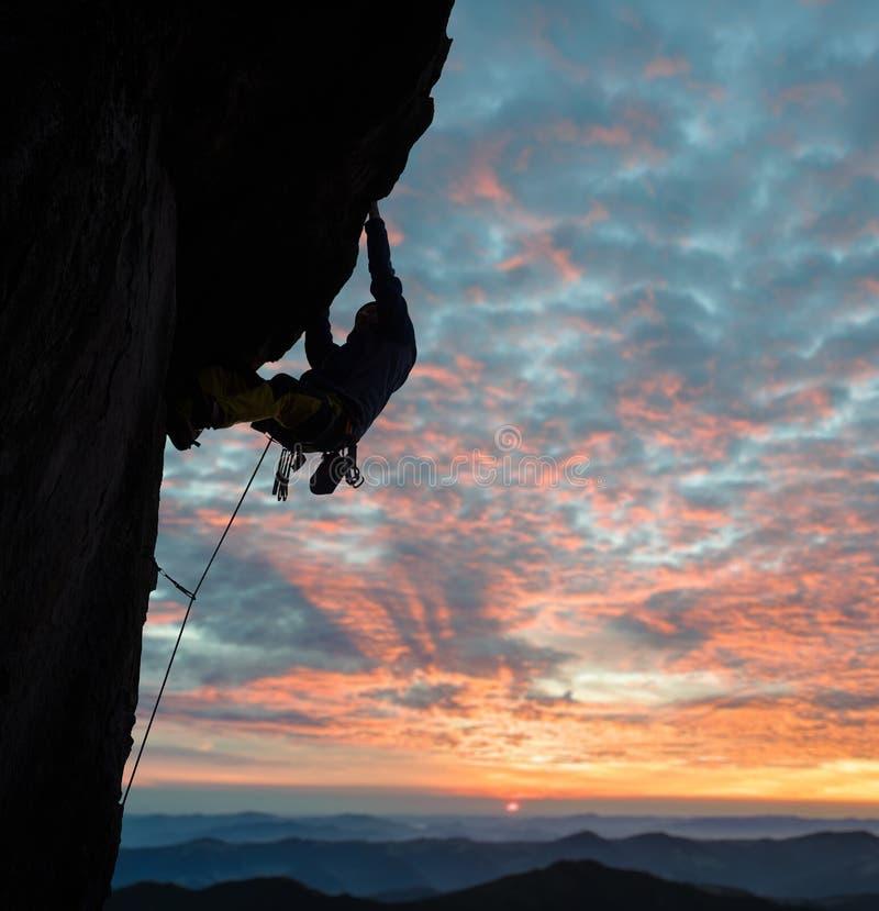 Vista lateral de la silueta del escalador en la acción en la puesta del sol sobre picos de montaña Nubes, cielo colorido en fondo foto de archivo