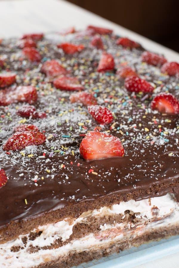 Vista lateral de la torta de chocolate cortada con las fresas frescas imágenes de archivo libres de regalías