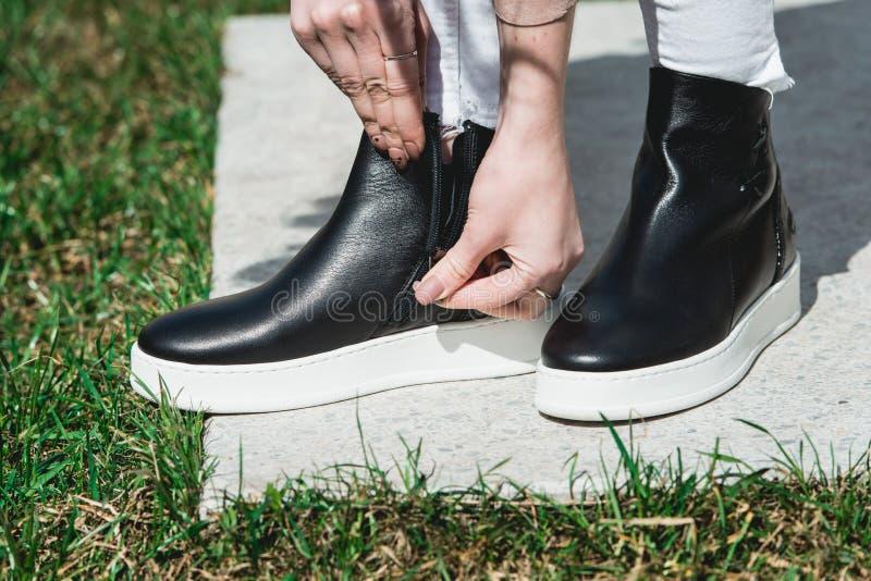 Vista lateral de las botas de cuero negras del tobillo de la mujer Tiro al aire libre sobre la piedra blanca en parque fotos de archivo libres de regalías