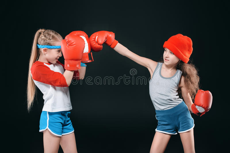 Vista lateral de las muchachas juguetonas que fingen el boxeo aislado en negro imágenes de archivo libres de regalías