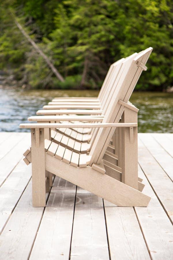 Vista lateral de las sillas de Muskoka en un muelle imagen de archivo libre de regalías
